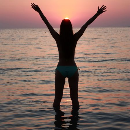 freedom - pretty young girl in a sea with wide open hands facing setting sun photo