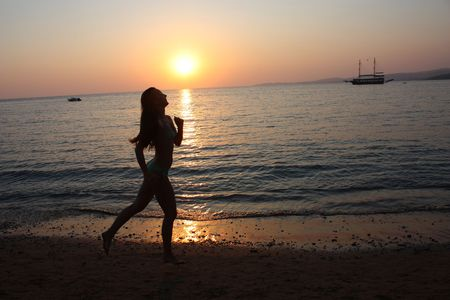 Woman running on the beach and sunset photo