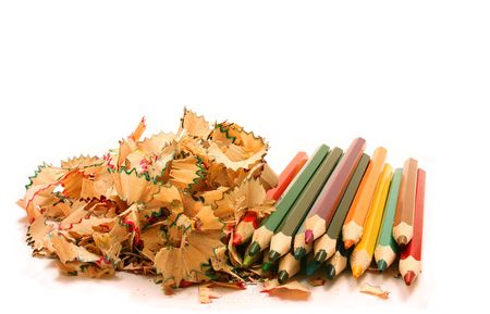 Colorful pencils and wood shavings on white background