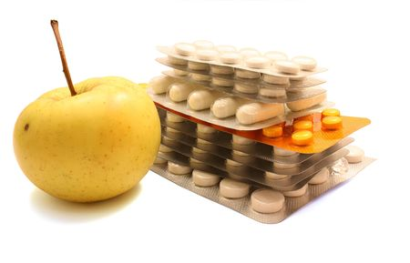 Packs of pills and yellow apple isolated on white background