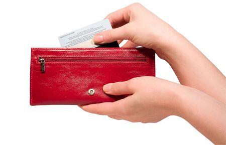 Woman hand pulling credit card out of a red purse -isolated over white background
