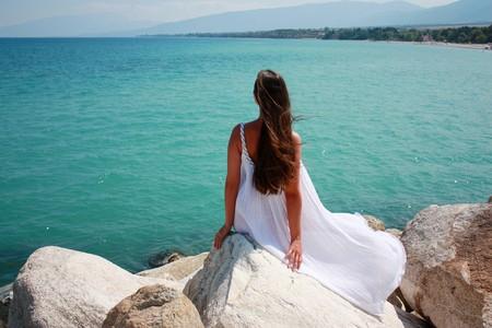Langharige meisje in witte jurk zitten door de zee Stockfoto
