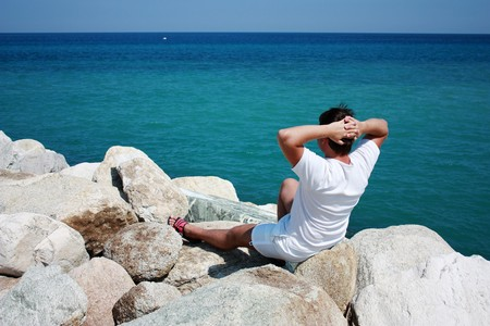 A man sitting on cliffs and enjoys the Aegean sea view photo
