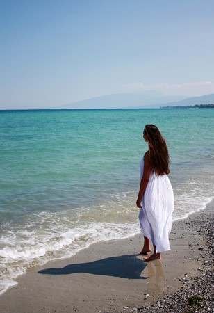 long: Beautiful woman in white long dress relax on the beach. Greece. Aegean Sea