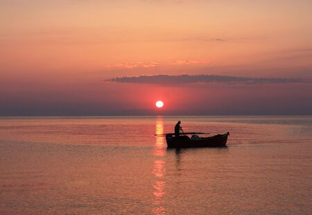 The setting sun silhouettes fishermen in a boat  Stock Photo
