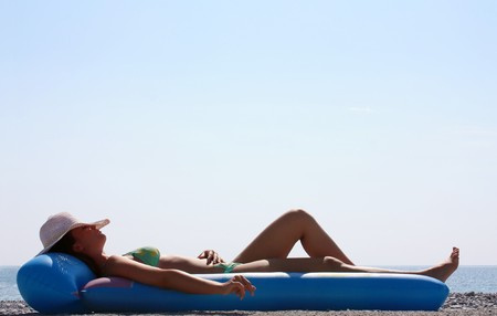 Woman in a green bikini lying on a inflatable beach mattress sunbathing with a straw hat over her head. photo