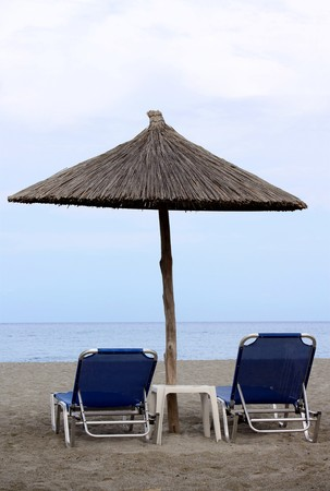 Beach umbrella and chairs on beach. Sea background photo