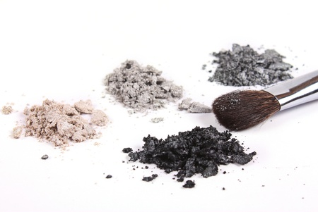 Cosmetics shadows and makeup brush on white background