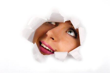 broken through: Young woman looking through hole in tearing paper Stock Photo