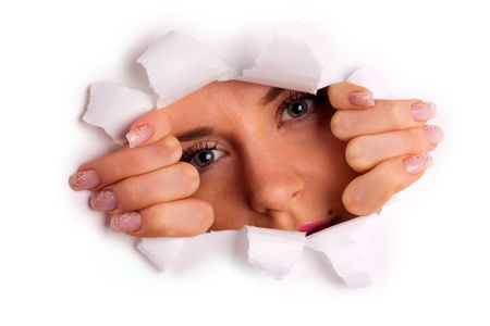 see through: Young woman looking through hole in tearing paper Stock Photo