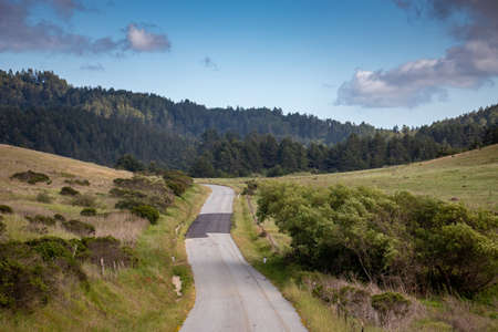 A road and green hills in the countryside near Pescadero, California