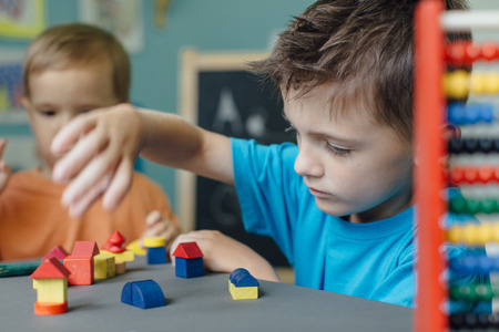 Two brothers playing with wooden blocks making houses learning shapes
