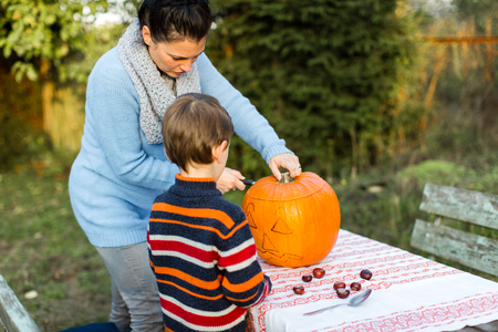 Mother and child carving pumpkin for Halloween