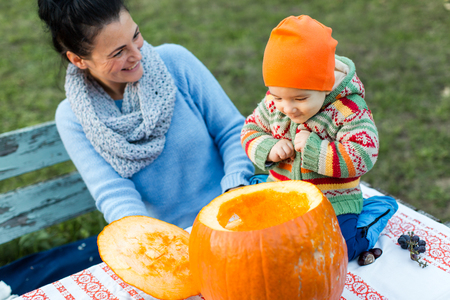 looking into: Happy baby looking into open Halloween pumpkin