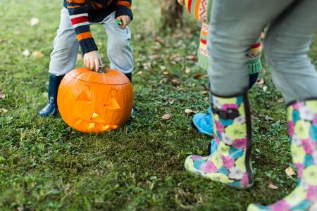 waist down: Close up of children hands and legs putting lid on Halloween pumpkin