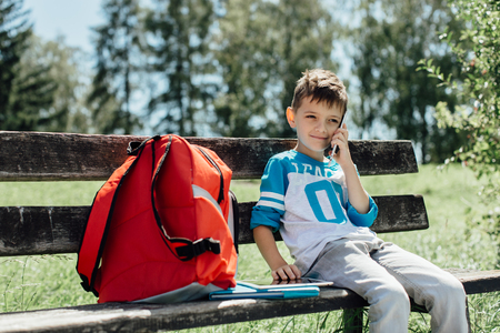 Schoolboy taking a break on a bench and making a phone call Stock Photo