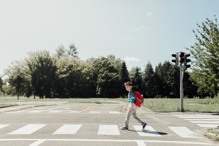 Schoolboy crossing a road on his morning way to school Фото со стока - 77458838