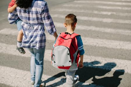 母と彼女の子供が朝学校へ行く途中の道路を横断する約
