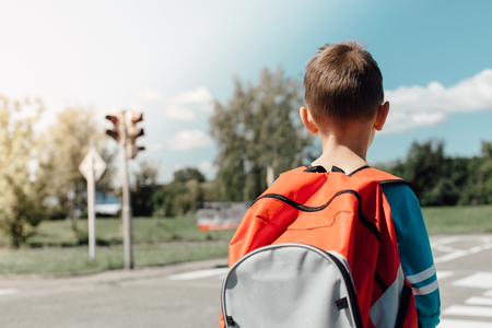Schoolboy standing and waiting at zebra crossing on his morning way to school