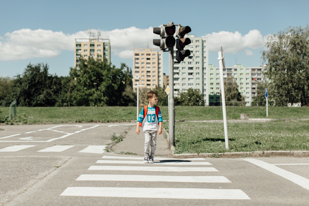 Schoolboy crossing a road on his morning way to school Фото со стока - 77458856