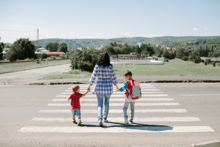 Mother and her children walking to school in the morning Фото со стока - 77458879