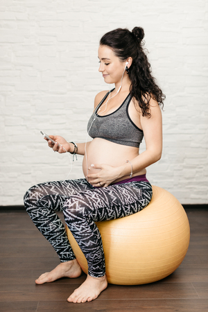 Pregnant woman exercising with a fitness ball and listening to music