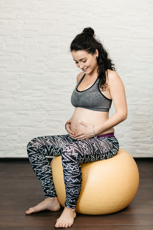 Happy pregnant woman sitting on a fitness ball and touching her belly