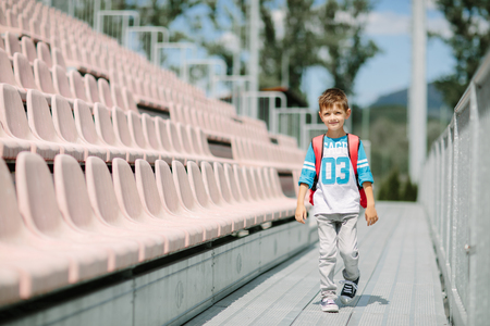 Portrait of a little schoolboy with a bag passing by rows of seats at a stadium