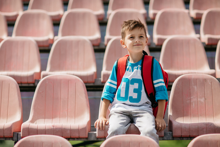 Portrait of a happy school boy sitting on a seat and watching a game