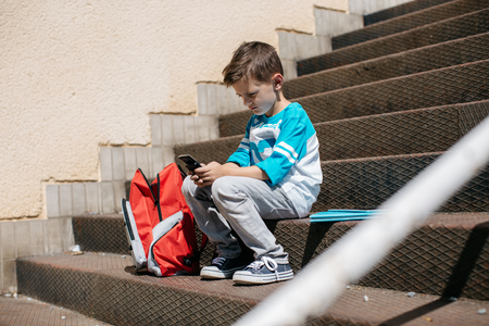 Child sitting outside school and playing games on his cell phone
