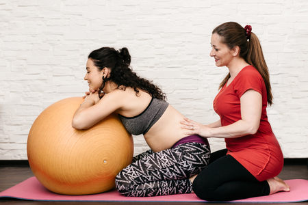 Midwife massaging a pregnant woman while exercising with a fitness ball Фото со стока - 84623876