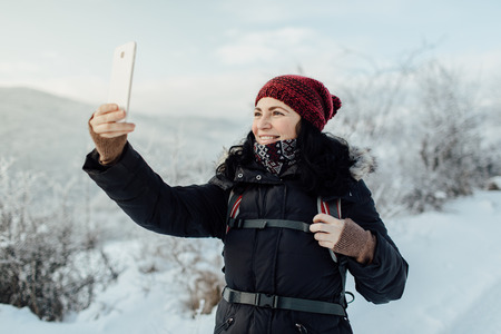 Happy female tourist taking pictures of frozen trees with a mobile Фото со стока