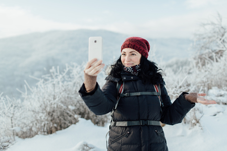 Happy female tourist having fun during a winter walk