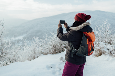 Female tourist taking pictures of frozen trees with her mobile