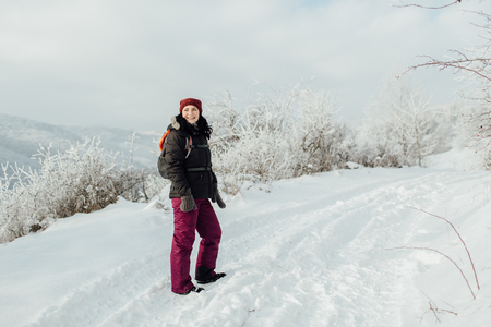 Happy female tourist standing on a snow trek and looking back