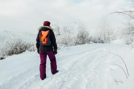 Back view of a woman dressed warm solo hiking in winter