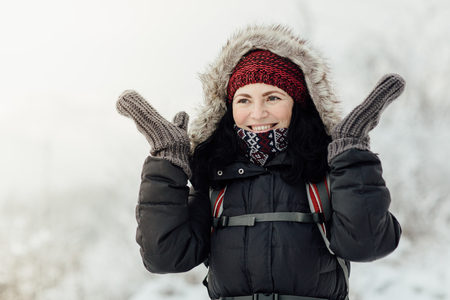 Portrait of a happy female tourist enjoying a snowy country