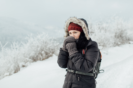 Portrait of a cheerful female tourist trying to keep warm in a snowy country
