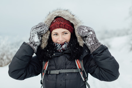 Happy female tourist trekking and enjoying a snowy day outside Фото со стока