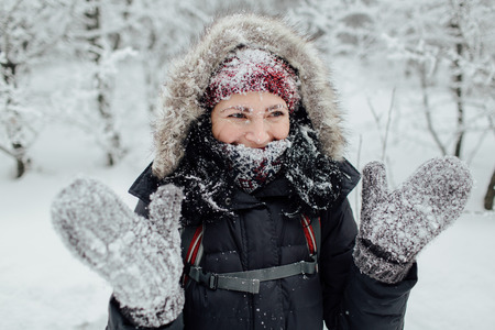Laughing woman dressed warm having fun in the snow Фото со стока