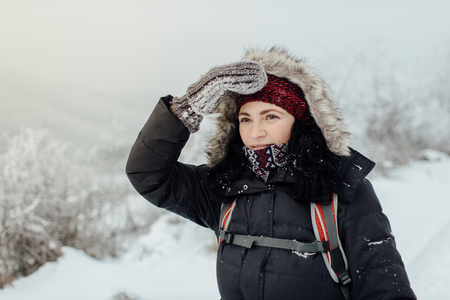Concerned woman dressed warm shielding her eyes during a winter walk