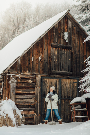 Portrait of a woman with a snow shovel standing in deep snow in front of a country house
