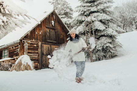 Portrait of a woman with a snow shovel removing snow from her yard at a country house