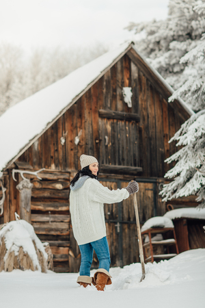 Snow removal - woman with a snow shovel standing in deep snow in front of a country house Фото со стока