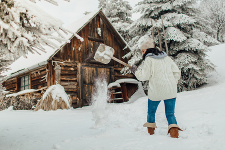 Portrait of a woman with a snow shovel shoveling deep snow in front of a country house Фото со стока - 93680259