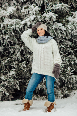 Portrait of a woman wearing gloves and hat standing in front of evergreen trees covered in snow