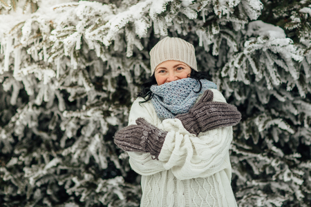 Portrait of a cheerful woman hugging herself in front of trees covered in snow Фото со стока