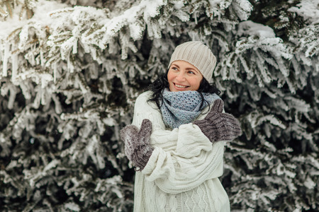 Portrait of a cheerful woman hugging herself in front of trees covered in snow Фото со стока - 93680263