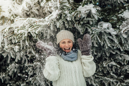 Portrait of a laughing woman standing under a snowy tree and enjoying snow shower Stok Fotoğraf