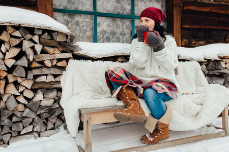 Portrait of a woman feeling cold on a snowy winter day drinking a hot drink Фото со стока